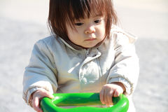 Japanese baby girl on the seesaw Royalty Free Stock Photos