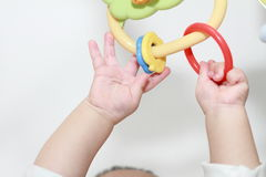 Japanese baby girl stretching her hands to the toy Stock Images
