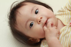 Japanese baby girl sucking her finger Royalty Free Stock Photos