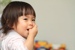 Japanese baby girl sucking her finger Stock Image