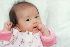 Japanese baby girl sucking her fingers Royalty Free Stock Photo