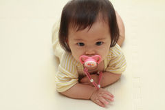 Japanese baby girl sucking on a pacifier Royalty Free Stock Photography