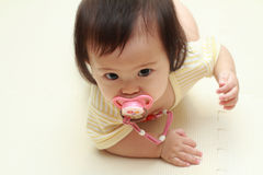 Japanese baby girl sucking on a pacifier Stock Image