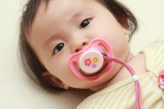 Japanese baby girl sucking on a pacifier Stock Photo