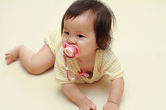 Japanese baby girl sucking on a pacifier Royalty Free Stock Image