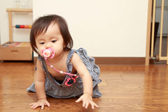Japanese baby girl sucking on a pacifier Royalty Free Stock Photo