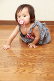 Japanese baby girl sucking on a pacifier Royalty Free Stock Images