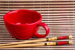 Japanese bamboo sticks of sushi, cup. Red cup, japanese sushi chopsticks on napkin bamboo background Royalty Free Stock Image