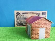 Japanese banknote, figure of a house on green surface and blue background. Backdrop for mortgage and housing value ads, loan for home construction and remodeling royalty free stock photo