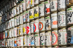 Japanese Barrels of Sake wrapped in Straw stacked on shelf Stock Photo