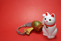 Japanese beckoning cat and lucky mallet close up in the red. Background royalty free stock photos