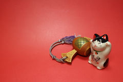 Japanese beckoning cat and lucky mallet in the red. Background royalty free stock image