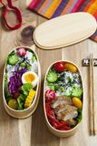 Japanese bento box with chicken, vegetables and rice. Japanese bento lunch box with chicken, cucumber, radish, red cabbage, pepper and rice stock image