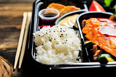 Japanese bento box ready to eat. Japanese bento box with rice, spicy mayo, gouza, grilled salmon teriyaki with vegetables. Complete with a side of wooden Royalty Free Stock Photos
