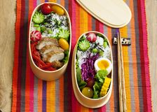 Japanese bento box with chicken, vegetables and rice. Japanese bento lunch box with chicken, cucumber, radish, red cabbage, pepper and rice royalty free stock photo