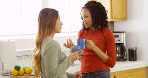 Japanese and black friends drinking coffee in kitchen stock photos