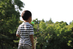 Japanese boy blowing bubbles. (4 years old Royalty Free Stock Photos