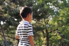 Japanese boy blowing bubbles. (4 years old Royalty Free Stock Images