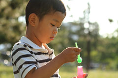 Japanese boy blowing bubbles. (4 years old Stock Photos