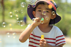 Japanese boy blowing bubbles. (4 years old Royalty Free Stock Photo
