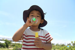 Japanese boy blowing bubbles Stock Photos