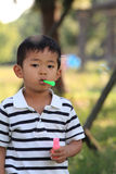 Japanese boy blowing bubbles. (4 years old Royalty Free Stock Image
