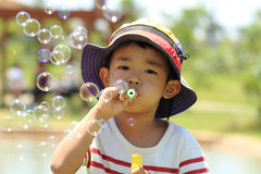 Japanese boy blowing bubbles. (4 years old Stock Photo