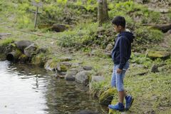 Japanese boy catching fish. Fourth grade at elementary school stock photo
