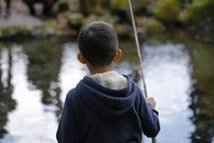 Japanese boy catching fish stock photos