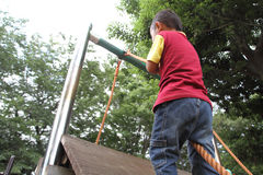 Japanese boy climbing on the wall Royalty Free Stock Photography