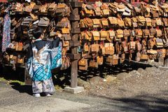 Japanese boy hanging an ema tablet. Japanese boy hanging an ema wooden tablet in a temple royalty free stock photography