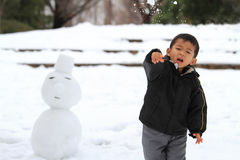 Japanese boy having snowball fight and snowman Stock Photo