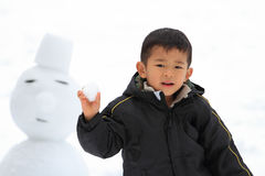 Japanese boy having snowball fight and snowman Stock Photos