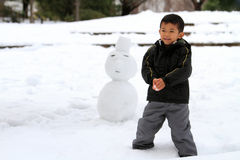 Japanese boy having snowball fight and snowman. (4 years old royalty free stock image