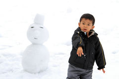 Japanese boy having snowball fight and snowman Royalty Free Stock Photo