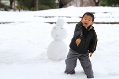 Japanese boy having snowball fight and snowman Royalty Free Stock Images