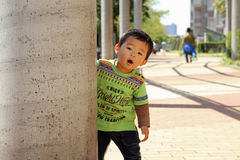 Japanese boy hiding behind the pole Royalty Free Stock Images
