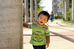 Japanese boy hiding behind the pole Royalty Free Stock Photography