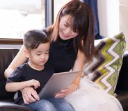 Japanese mother and boy watching internet contents, using tablet device Stock Photography