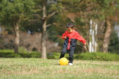 Japanese boy kicking a yellow ball Royalty Free Stock Image