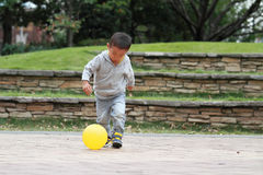 Japanese boy kicking a yellow ball Royalty Free Stock Photo