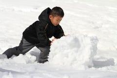 Japanese boy making snowman Royalty Free Stock Photo