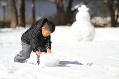 Japanese boy making snowman Royalty Free Stock Photos