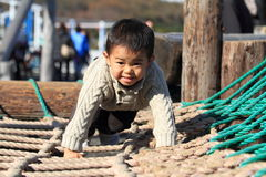 Japanese boy playing at field athletic Royalty Free Stock Image