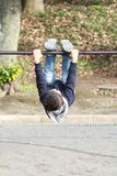 Japanese boy playing with high bar Royalty Free Stock Images