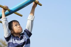 Japanese boy playing with a monkey bars stock photos