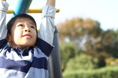 Japanese boy playing with a monkey bars royalty free stock photo