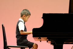 Japanese boy playing a piano Royalty Free Stock Images