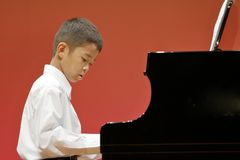 Japanese boy playing piano on stage stock photos