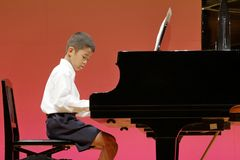 Japanese boy playing piano on stage stock photography